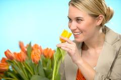 嗅到一黄色郁金香春天花的妇女 免版税库存图片
