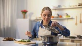 嗅到与恶心的面孔表示的年轻女人煮熟的汤,被损坏的食物 股票录像