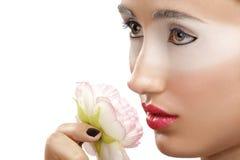 嗅到与白色眼影膏构成的美丽的女孩一朵花 免版税库存照片