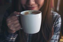 嗅到和喝与感到的亚裔妇女的特写镜头图象热的咖啡好 免版税库存照片