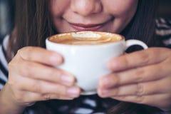 嗅到和喝在白色杯子的亚裔妇女的特写镜头图象热的咖啡有感到的好 库存照片