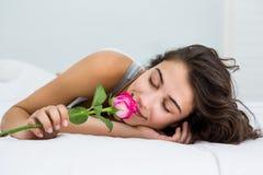 嗅到在床上的妇女一朵玫瑰花 免版税库存图片