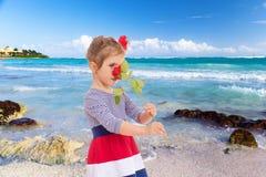 嗅到在海滩的女孩一朵玫瑰 免版税库存图片