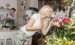 嗅到在花店的金发碧眼的女人一朵玫瑰 免版税库存图片