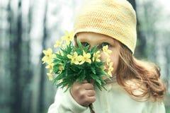 嗅到在绿色背景的女孩特写镜头一朵黄色花愉快 库存图片