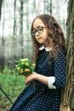 嗅到在绿色背景的女孩特写镜头一朵黄色花愉快 免版税库存照片