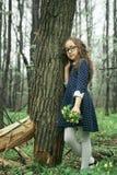 嗅到在绿色背景的女孩特写镜头一朵黄色花愉快 免版税库存图片