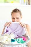 嗅到她的洗衣店的妇女 免版税库存图片