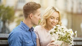 嗅到好的花,从心爱的男朋友,浪漫日期的礼物的愉快的女孩 免版税库存图片