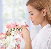 嗅到妇女的美丽的花 库存照片