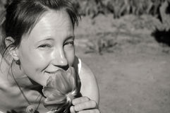 嗅到玫瑰的美丽的白肤金发的少妇俏丽的女孩画象的黑白关闭,看照相机 库存照片
