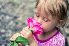 嗅到玫瑰的美丽的问候孩子 库存图片