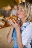 嗅到甜食物的女职工 免版税库存图片