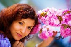 嗅到美丽的佐仓开花,紫色花的少妇 春天魔术 免版税库存图片
