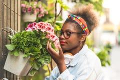 嗅到花的两个十几岁的女孩 免版税图库摄影