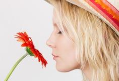 嗅到花的新白肤金发的妇女 库存图片
