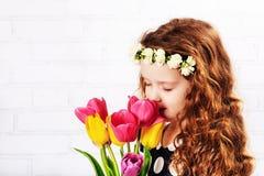 嗅到郁金香的花束甜女孩 库存照片