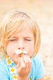 嗅到雏菊的愚蠢的矮小的白肤金发的女孩 免版税图库摄影