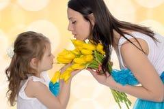嗅到黄色郁金香的母亲和女儿 免版税库存图片