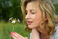 嗅在领域的女孩狂放的野花 免版税库存图片