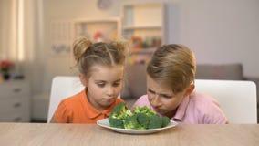嗅新鲜的硬花甘蓝,引不起食欲的膳食,无味的健康食品的两个孩子 影视素材