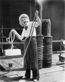 嗨,从水手的成套装备的一个少妇,拿着一条重的绳索(所有人被描述不是更长的生存和没有庄园exi 免版税库存照片