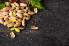 嘎吱咬嚼的开心果顶视图在黑桌背景的 开心果和蓬蒿叶子快餐的 复制空间 免版税库存图片