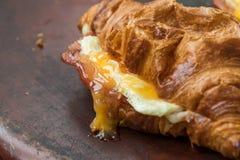嘎吱咬嚼的火腿和乳酪新月形面包早餐 免版税库存照片