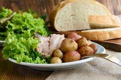 嘎吱咬嚼的烘烤带皮烤的土豆和被烘烤的猪肉 图库摄影