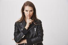 嘘,听我 握在嘴的可爱的美丽的欧洲妇女食指,看肉欲上照相机 库存图片