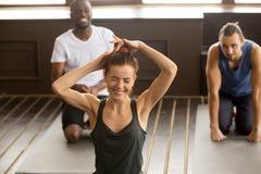 嘲笑不同种族的小组健身瑜伽分类的滑稽的少妇 免版税库存图片
