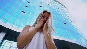 嘲笑与摩天大楼的年轻白肤金发的妇女低角度照相机背景的 股票视频