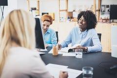 嘲笑业务会议的美丽的妇女在现代办公室 编组一起谈论女孩的工友新的时尚项目 贺尔 库存照片