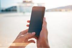嘲笑使用她的智能手机的女孩为旅行 免版税图库摄影