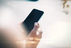 嘲笑使用她的智能手机的女孩在城市 库存照片