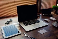 嘲笑办公室或家庭桌面有小配件的并且工作工具,黑屏便携式的便携式计算机, 库存照片