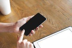 嘲笑图象拿着有黑屏的妇女手智能手机 库存照片