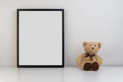 嘲笑在桌上的照片框架与玩具熊作为装饰 免版税库存图片