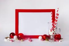 嘲笑在白色背景的红色框架与圣诞节装饰和candys 文本的,邀请,贺卡,纸地方 免版税库存照片