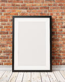 嘲笑在老砖墙和木地板,背景上的空白的黑画框 库存图片