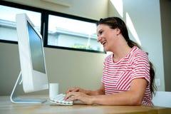 嘲笑她的计算机的微笑的妇女 库存图片