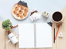 嘲笑开放笔记本、纸工艺、立方体日历、烤红萝卜与可怕面孔和咖啡杯 图库摄影