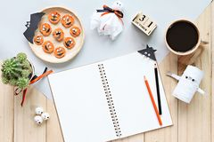嘲笑开放笔记本、纸工艺、立方体日历、烤红萝卜与可怕面孔和咖啡杯 免版税库存图片