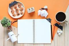 嘲笑开放笔记本、纸工艺、立方体日历、烤红萝卜与可怕面孔和咖啡杯 库存照片