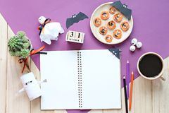 嘲笑开放笔记本、纸工艺、立方体日历、烤红萝卜与可怕面孔和咖啡杯 免版税库存照片