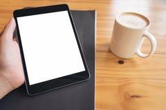 嘲笑拿着有白色黑屏和咖啡杯的手的图象黑片剂个人计算机在木桌背景 库存图片