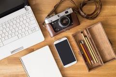 嘲笑有膝上型计算机和电话的摄影师书桌 免版税库存照片