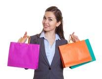 嘲笑照相机的时髦的女人在购物以后 免版税库存照片
