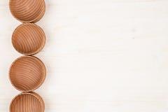 嘲笑的设计观念在白色木背景的空的木米黄碗 免版税库存照片