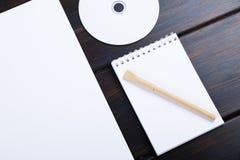 嘲笑空白的笔记本, CD的盘,笔,在木书桌上的纸名单 免版税库存照片